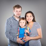 Mother and Father holding son in a family studio portrait