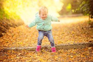 littel-girl-jumping-autumn-leaves-family-portraits