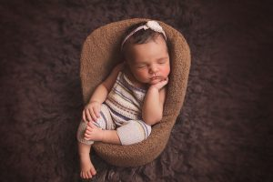 newborn-baby-girl-sleeping-in-chair-with-dungarees