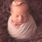 Newborn baby girl wearing a headband, swaddled in grey wrap