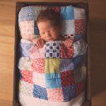 newborn baby boy sleeping in a wooden bed