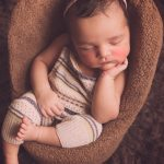 Newborn baby girl with wearing dungarees sleeping in a chair.