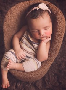 newborn-baby-girl-sleeping-in-chair-wearing-dungarees