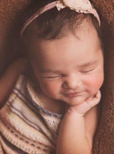 newborn baby girl sleeping smiling