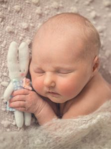 newborn baby girl sleeping with teddy in her hand