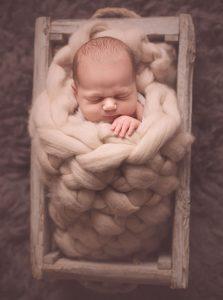 newborn-boy-sleeping-in-fluffy-wool
