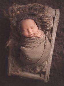newborn-boy-slppeing-in-wooden-bed-wears-a-teddy-bear-hat