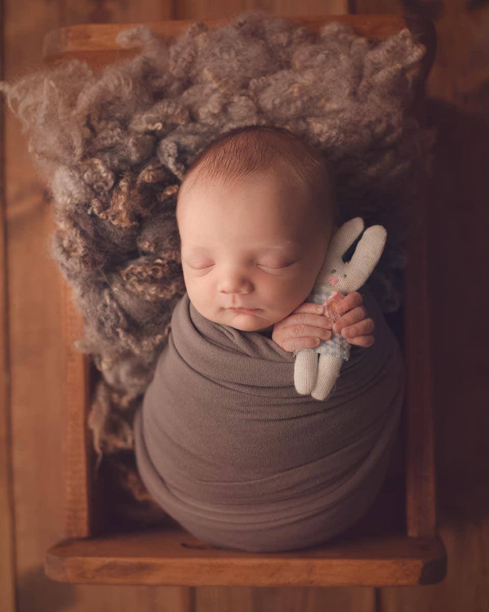Newborn baby sleeping in wooden bed holding a teddy bear.