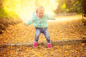 littel-girl-jumping-autumn-leaves-family-portraits