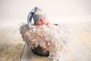 newborn-baby-girl-sleeping-wooden-trug