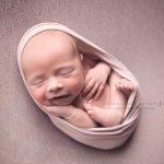 Glasgow newborn studio session with smiling baby boy.