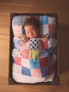 newborn-baby-boy-sleeping-wooden-bed