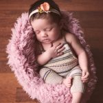 Newborn baby girl with dark brown hair sleeping in a chair and smiling