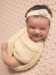 newborn-baby-girl-swaddled-smiling