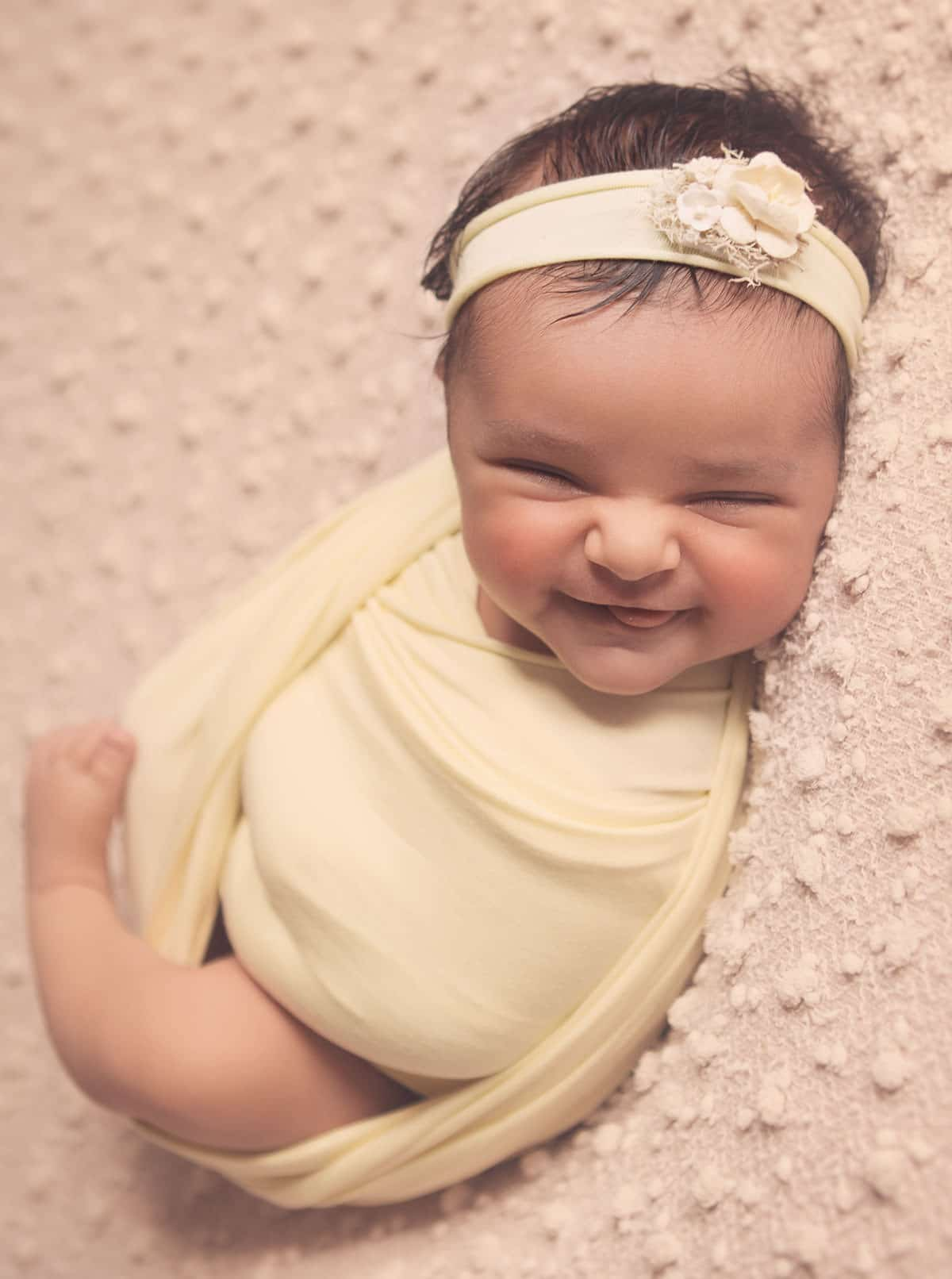Newborn baby girl swaddled in yellow blanket smiling.