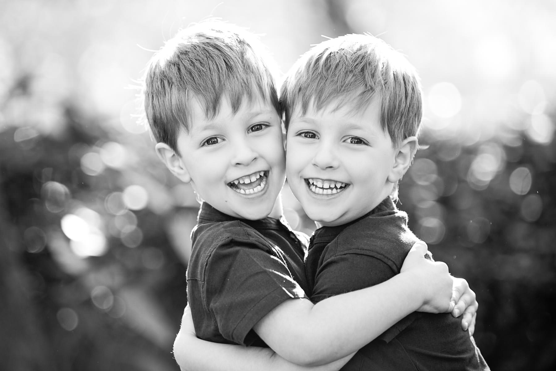 Twin brothers hugging and smiling