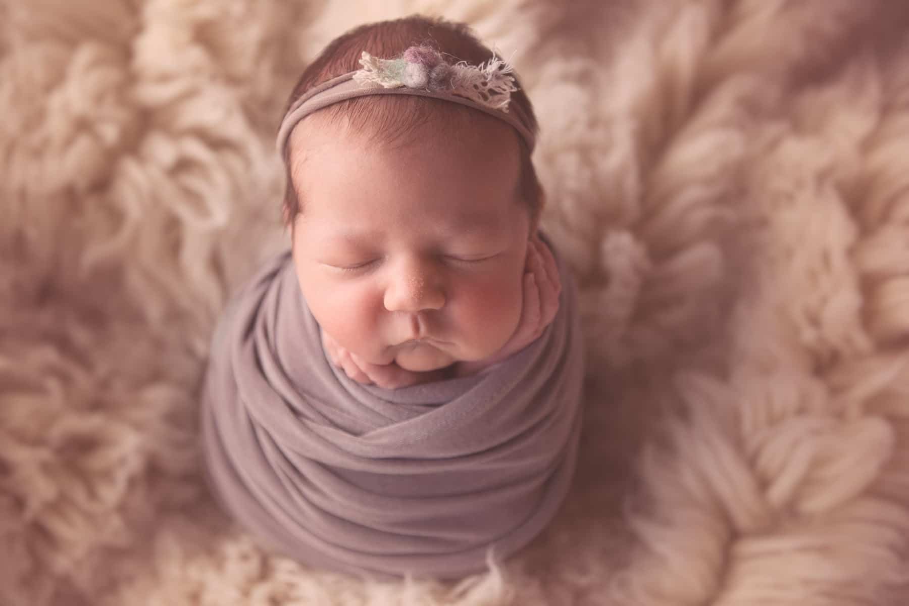 newborn baby swaddled with hands on cheeks