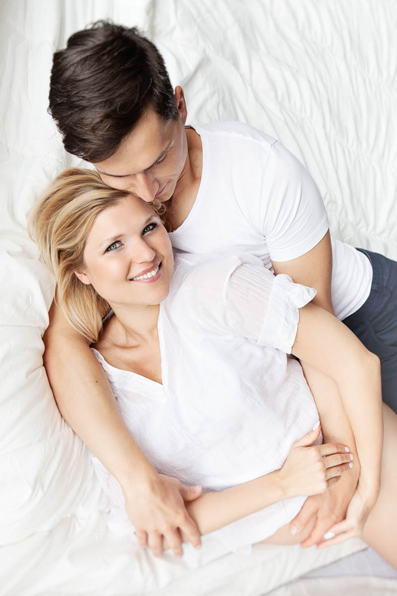 man and woman hugging on white bed