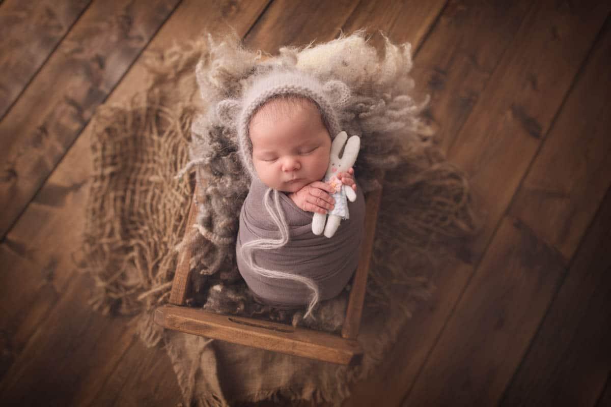 Newborn baby girl sleeping in wooden bed.