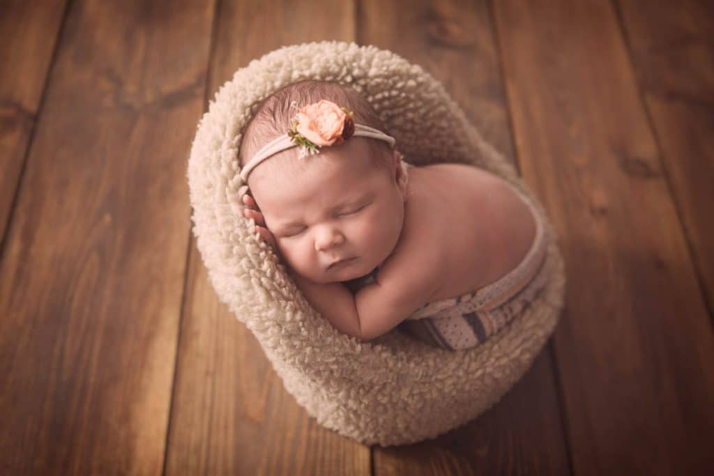 Newborn baby girl sleeping in posing chair