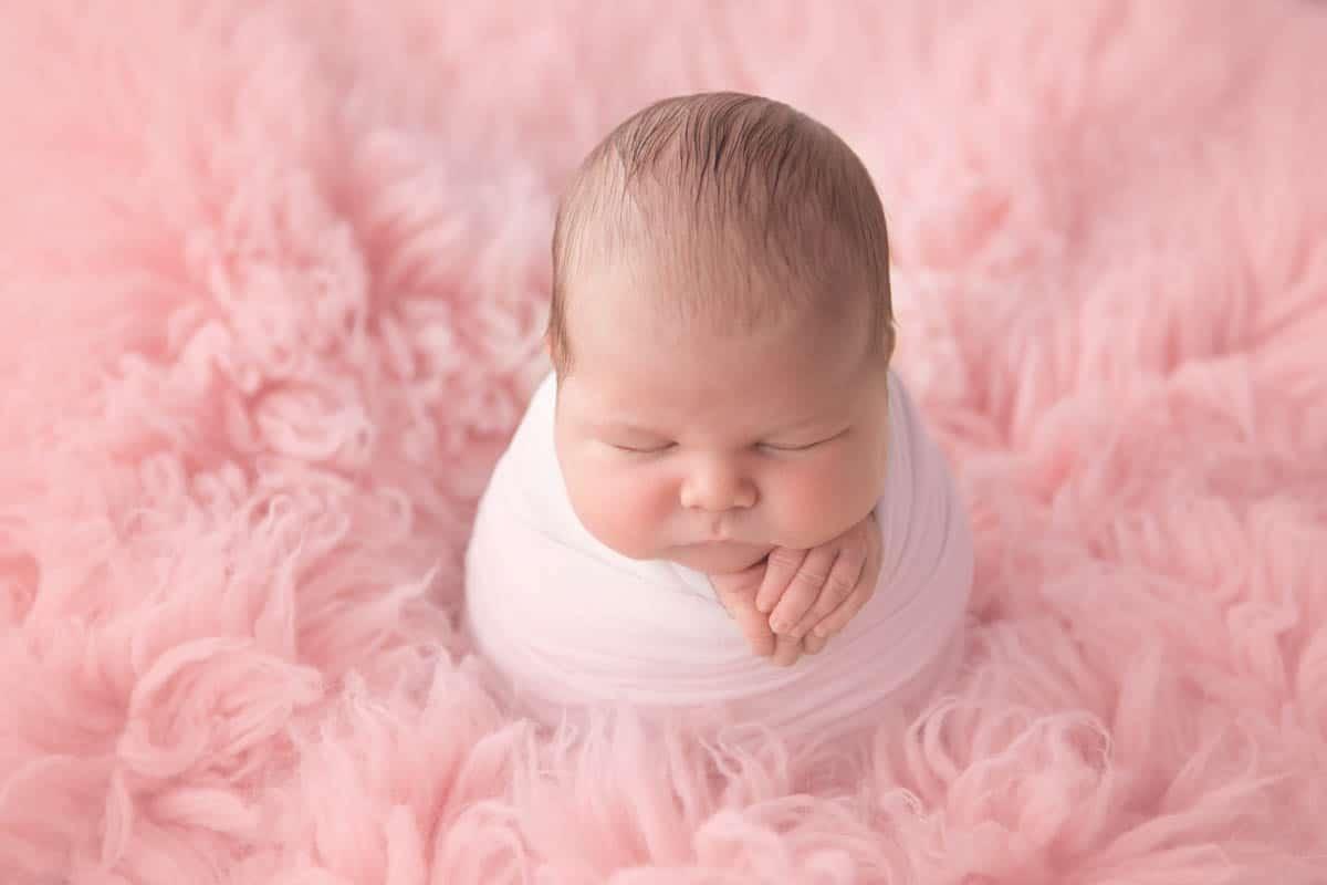 Newborn baby girl on pink flokati rug