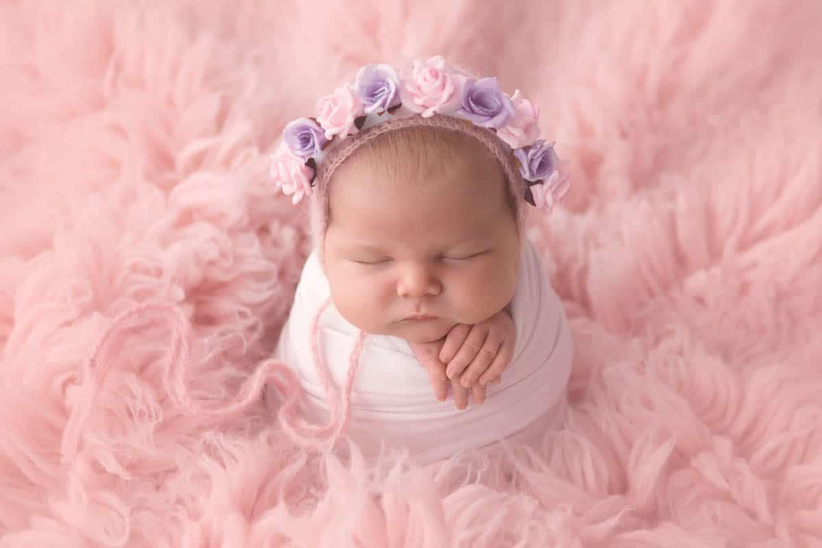 Newborn baby girl in potato sack pose on pink rug