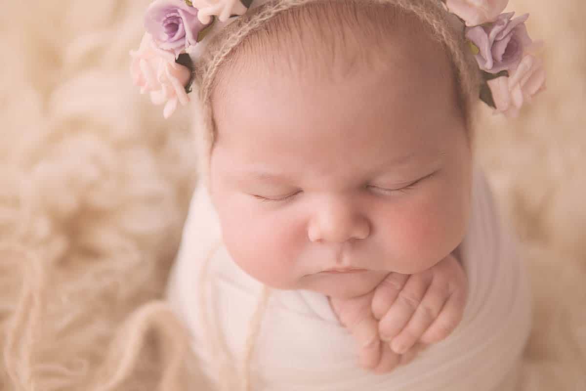Portrait of newborn baby girl wearing floral hat