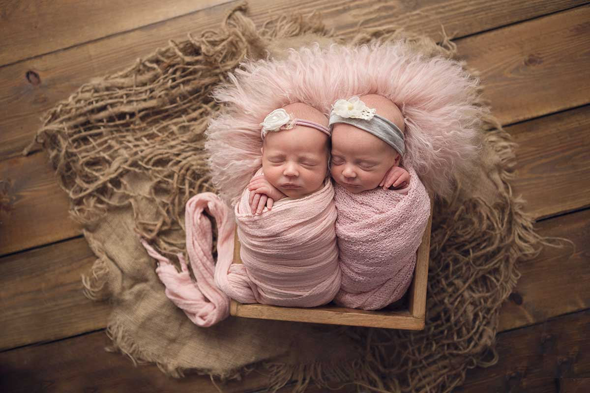 newborn twins in matching pink outfits photographed by dawn martin photography