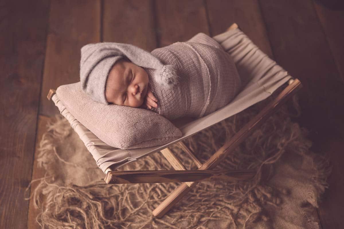 newborn baby girl snoozing in hammock
